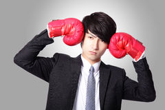 Business man hitting himself by boxing glove Royalty Free Stock Photo