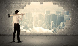 Business man hitting wall with hammer on city view. Background stock photos