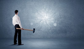 Business man hitting wall with a hammer. Business man hitting grungy wall with a hammer Royalty Free Stock Photos