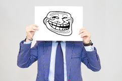Business man hoding card with troll face on grey background Stock Photography