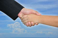 Business man hold boy hand. In helping hand concept stock images