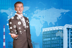 Business man hold cloud icons. Building as. Business man hold cloud icons in hand. Building and world map as backdrop Royalty Free Stock Photography