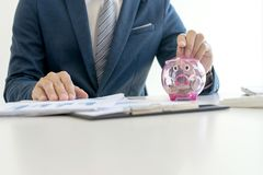 Business man hold collect coin in the row. In front of the saving box concept economy investment Stock Image