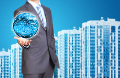 Business man hold Earth. New houses row as Stock Image