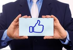 Business man hold paper thumb up icon on it Royalty Free Stock Photography