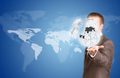 Business man hold exploding ball of gray puzzle. Pieces in hand. World map as backdrop Stock Photography