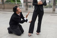 Business man hold female boss leg. Stress Business man  kneel and hold his woman boss leg to ask for sympathy after  he not get promote or be punished outside Royalty Free Stock Photos