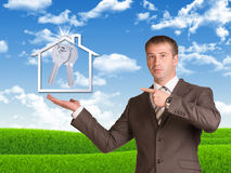 Business man hold house icon and metal keys in Stock Photos