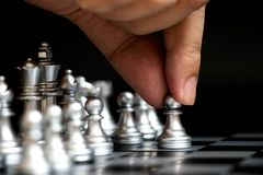 Business man hold pawn to first move in chess game. Concept for company strategy, vision or decision Stock Photo