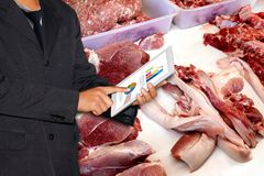 Business man hold Tablet and fresh Pork in Market, Pork Trading Business stock photo