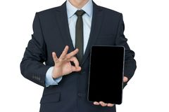 Business man hold the tablet and show ok sing by his hand. mock up Royalty Free Stock Images