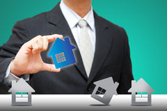 Business man Hold the tiny house icon Royalty Free Stock Photo