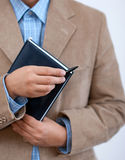 Business man holding agenda. Royalty Free Stock Photo