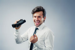 Business man with binocular. Business man holding binocular expressing emotions Royalty Free Stock Images