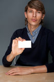 Business man holding blank. Portrait of young handsome business man holding blank white business card while sitting relaxed at his office stock image