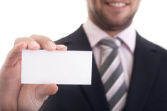 Business man holding a blank business card. Closeup of business man holding a blank business card Royalty Free Stock Photography