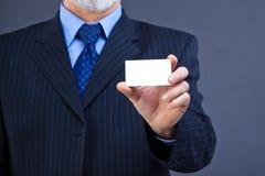 Business man holding blank card. Studio shot of a business man holding blank visit card Stock Photo