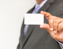 Business man holding a blank card where you can place text. Business person over a white background holding a business card with h Royalty Free Stock Images