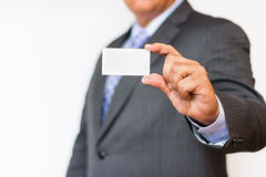 Business man holding a blank card where you can place text. Business person over a white background holding a business card with h Royalty Free Stock Photo