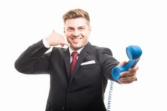 Business man holding blue telephone receiver showing contact ges Royalty Free Stock Photos