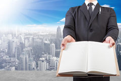 Business man holding book blank at high building construction si Stock Images