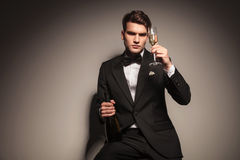 Business man holding a bottle and a glass of champagne. Stock Photography
