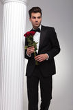 Business man holding bouquet of red roses in his hand. Handsome young business man posing near a white column with a bouquet of red roses in his hand, looking Stock Photo
