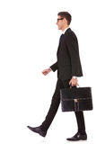 Business man holding brief case and walking Royalty Free Stock Photo