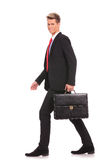 Business man holding brief case and walking Stock Photo
