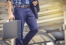 Business man holding a briefcase walking up the stairs in the routine of working with determination and confidence. stock photos