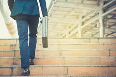 Business man holding a briefcase walking up the stairs in the routine of working with determination and confidence. royalty free stock image