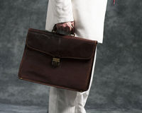Business man holding briefcase. Business man in white suit holding briefcase Royalty Free Stock Images