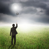Business man holding bulb balloon in fields and raincloud Stock Photo