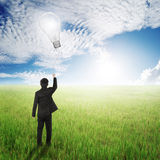 Business man holding bulb balloon in fields and sun sky Royalty Free Stock Photography