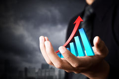 Business man and holding business growth. Hand holding a rising arrow, representing business growth Stock Image