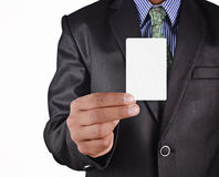 Business man holding card in black suit isolated on white backgr. Ound Royalty Free Stock Photography