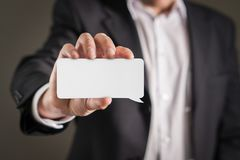 Business man holding business card. Business man holding empty white business card stock images