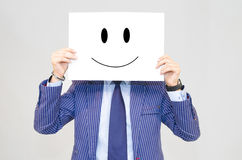 Business man holding card with happy face on grey background Stock Photo