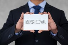 Business man holding a card with thank you text. Digital composite of Business man holding a card with thank you text Stock Photo
