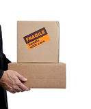 Business man holding cardboard moving box on white. Business man holding a brown corrugated, cardboard moving box on white with copy space Stock Photography