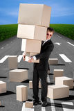 Business man holding carton boxes on the road. With a lot of boxes royalty free stock photos