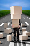 Business man holding carton boxes on the road with a lot of boxe Royalty Free Stock Photography