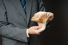 Business man is holding cash, fan of fifty euros. Person counts money. Businessman hands and euro bills Royalty Free Stock Image
