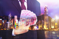 Business man holding Chinese money RMB on blurry background. Royalty Free Stock Photos