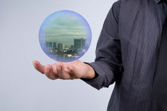 Business man holding a city inside a sphere, City of the future Royalty Free Stock Photography