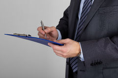 Business man holding clipboard and signing documents Stock Photos