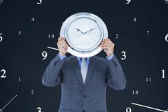Business man holding a clock against background with clocks. Digital composite of Business man holding a clock against background with clocks Royalty Free Stock Image