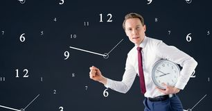 Business man holding a clock against background with clocks Stock Image