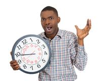 Business man holding a clock, pressured by lack of time running out Royalty Free Stock Image