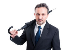 Business man holding closed umbrella on his shoulder Stock Photo